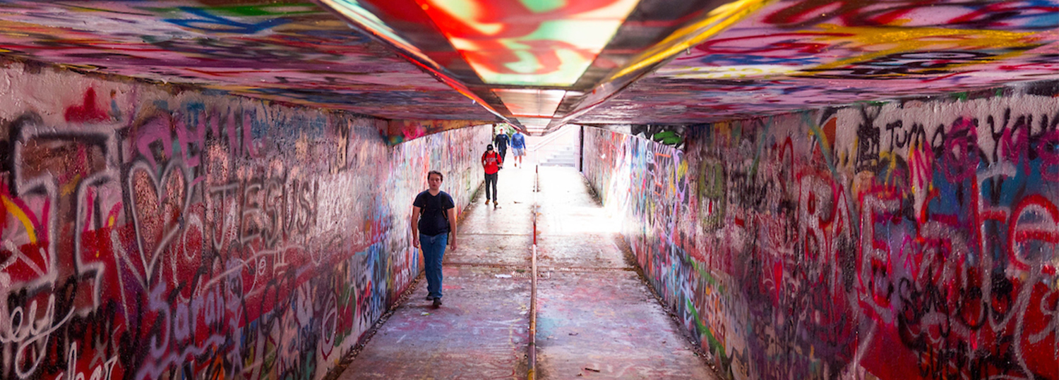 students walk through painted tunnel