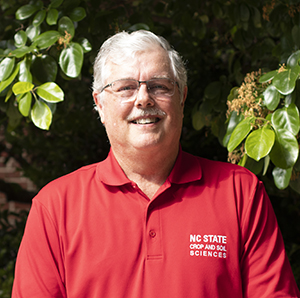 Man in red shirt standing in front of trees